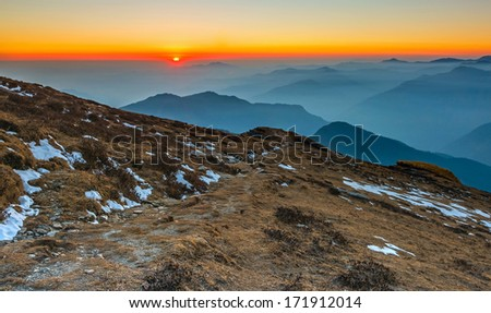 sunset scene with a path at hill slope  - stock photo
