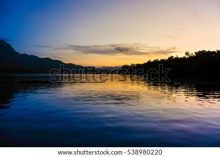 Sunset Scene with Beautiful lake and mountain background at Ratchaprapa dam , khao sok national park ,Thailand