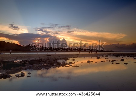 Sunset scene with mirror reflection on a tropical sea beach in Bali. Orange sunset sky on a beach. Tranquil sunset, Bali. Soft sunset, Bali. Amazing sea sunset. Sunset sea view. Peaceful sunset.  - stock photo