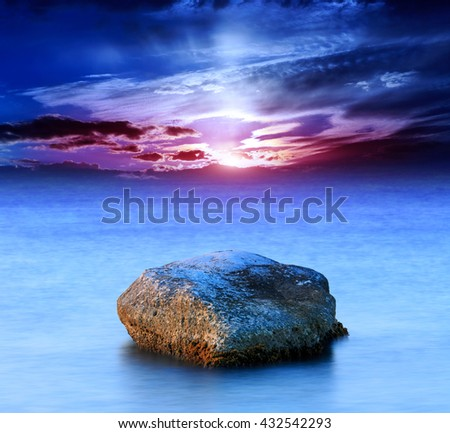 Sunset scene with stone in sea water
