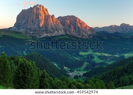 Sunset scenery of rugged Sassolungo-Sassopiatto mountains with alpenglow & a village in green grassy valley in Col Raiser, Val Gardena, Dolomiti National Park, South Tyrol, Italy, Europe (in Ortisei) - stock photo