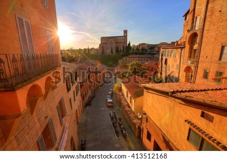 Sunset scenery of Siena, a beautiful medieval town in Tuscany, Italy, with view of a peaceful street leading to San Domenico Church ( St. Dominic Basilica ) in the background - stock photo