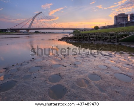 """Sunset scenery of the landmark """"Dazhi"""" Bridge spanning over Keelung River in Taipei City, Taiwan ~A beautiful cable-stayed suspension bridge at rosy dusk with reflections of golden clouds on the water - stock photo"""