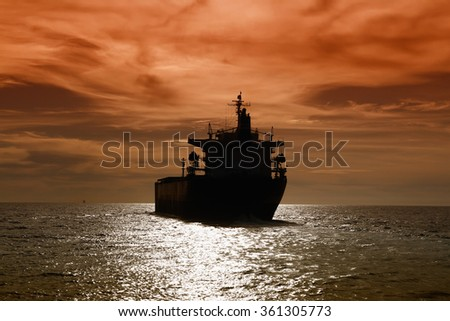 Sunset seascape and bulk-carrier ship sailing