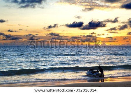 Sunset seascape.Beach and sports.water scooter - stock photo