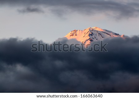 Sunset sets Shasta Mountain aglow as it rises above a late winter storm.  - stock photo