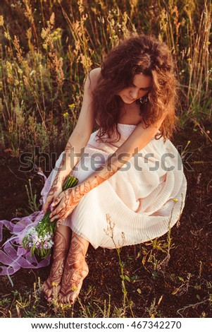 Sunset shines over a woman sitting on the cold ground