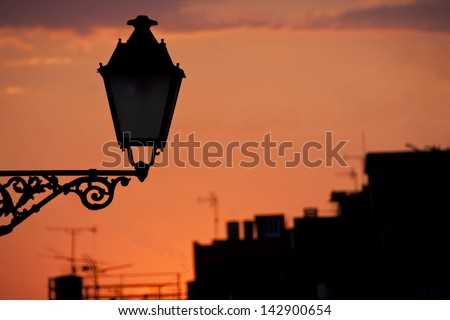 Sunset silhouette of a street lamp with industrial background, Spain. - stock photo