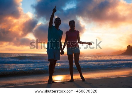 sunset silhouette of young couple in love at beach - stock photo