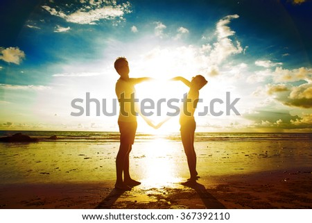 sunset silhouette of young couple in love holding hands at beach - stock photo