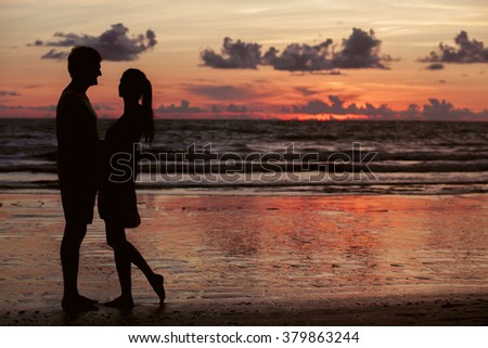 sunset silhouette of young couple in love hugging at beach - stock photo