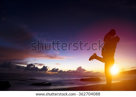 sunset silhouette of young couple in love hugging on beach - stock photo