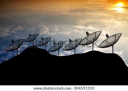 Sunset Silhouette  Satellite dish on hill  - stock photo