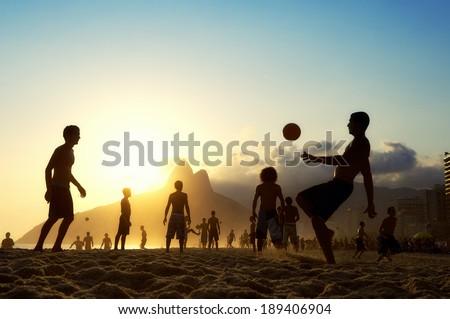 Sunset silhouettes playing altinho futebol beach football kick-ups soccer ball Ipanema Beach Rio de Janeiro Brazil - stock photo