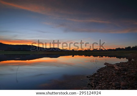 Sunset skies over Boorooberongal Lake in Penrith Castlereagh with Blue Mountains in distance - stock photo