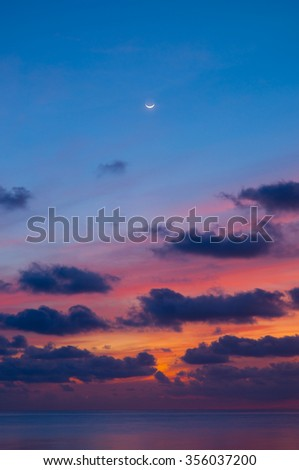 Sunset sky and sea at dusk with crescent moon