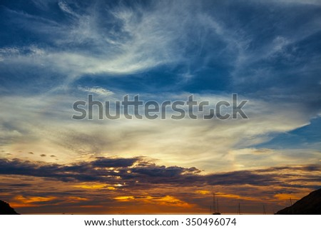 Sunset sky, lit in colors of blue, orange, lavender and gray, stretched out over the horizon of a tropical seascape. - stock photo
