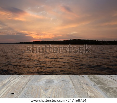 Sunset sky over lake with wooden planks floor on foreground