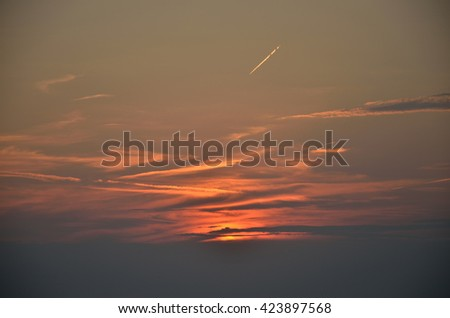 Sunset sky with plane trace - stock photo