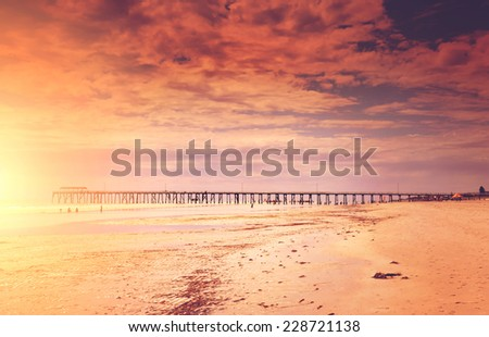 Sunset style seascape overlooking wide sandy beach and jetty pier in background. - stock photo