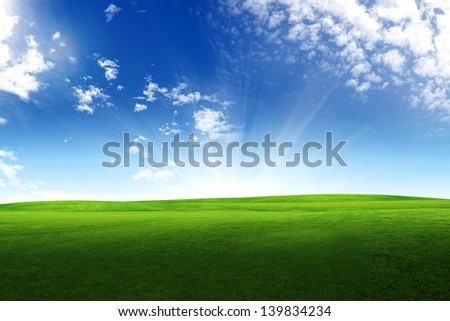 Sunset sun and Field of grass and sunny sky - stock photo