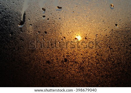 sunset sun through water drops on glass background - stock photo