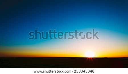 Sunset, Sunrise, Sun Over Rural Countryside Field. Bright Clear Sky And Dark Ground. Panoramic View