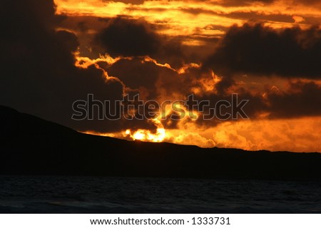 Sunset through a skyscape over the island of Taransay, Western Isles, Scotland