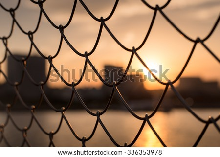 sunset through the fence  - stock photo