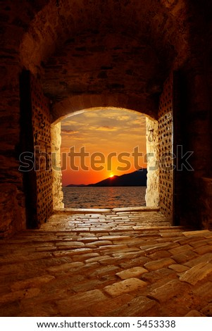 Sunset through the old castle - stock photo