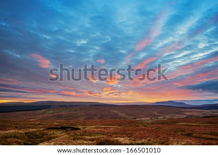 Sunset view across moorland to the Pennines in the Yorkshire Dales. The distinctive, plateaued peak of Ingleborough, one of the famous three peaks, can be seen on the horizon. - stock photo