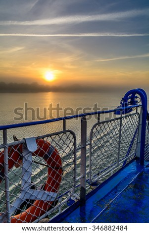 Sunset view from the edge of a boat's deck. Vertical view of a foggy sun-setting background in a summer evening, from the edge of deck.