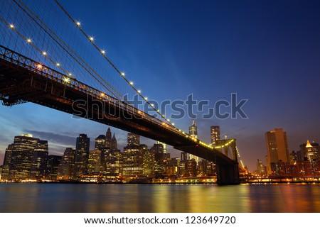 Sunset view Lower Manhattan skyline with Brooklyn Bridge in New York City - stock photo