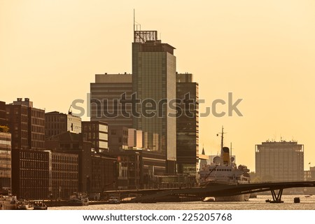 Sunset view of Amsterdam with modern buildings alongside the river IJ - stock photo