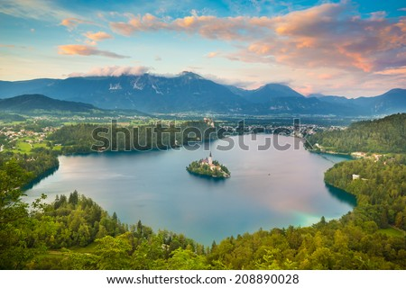 Sunset view of Julian Alps and Lake Bled with St. Marys Church of the Assumption on the small island. Bled, Slovenia, Europe.  - stock photo