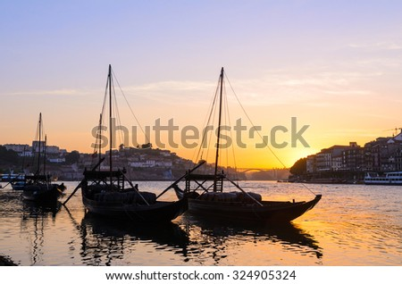 sunset view of traditional boats and Douro river in Porto, Portugal - stock photo