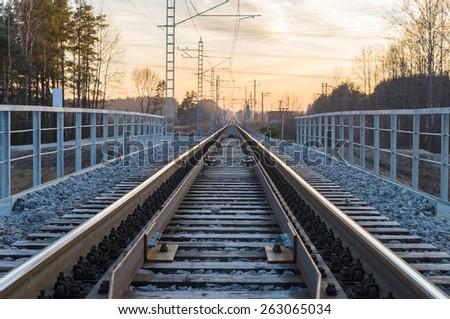 Sunset view on a electric railway vanishing to horizon - stock photo
