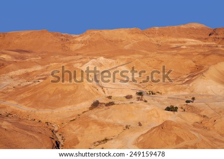 Sunset view on the desert valley from the walls of ancient Massada fortress - stock photo