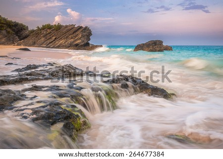 Sunset view over the Horseshoe Bay beach on Bermuda island with beautiful turquoise waves hitting the shore