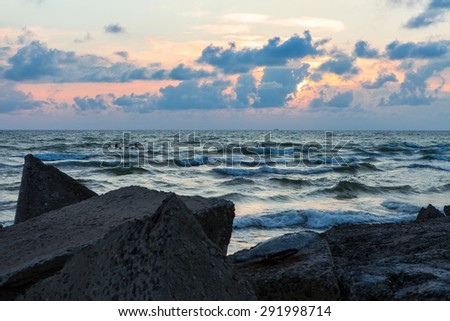 Sunset view over waves of  Baltic sea from break water on stormy weather - stock photo