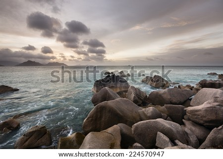 Sunset view to Praslin from La Digue, Seychelles with granite rocks in the foreground