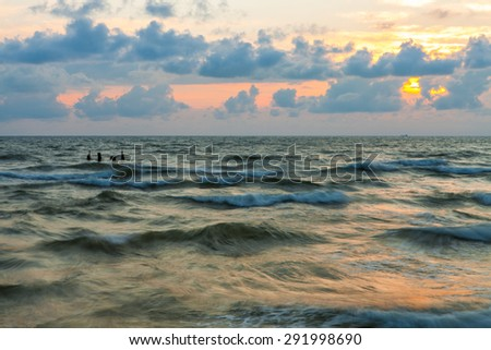 Sunset view with destroyed pier over waves of  Baltic sea on stormy weather - stock photo