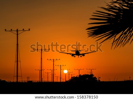 Sunset when a commercial jet lands at Airport - stock photo