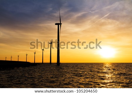 Sunset wind turbines in a row - stock photo