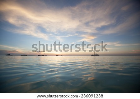Sunset with artisanal or traditional fishing dhows and reflections of the red, orange and blue sky reflected in the waters of the Indian Ocean  - stock photo