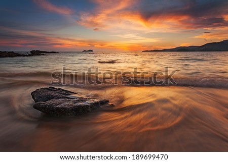Sunset with big rock - stock photo