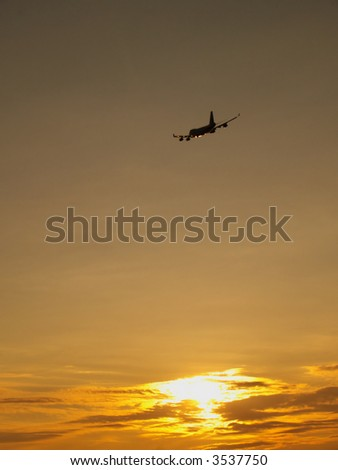 Sunset with clouds and aircraft in sky
