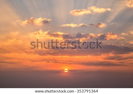Sunset with clouds, light rays and other atmospheric effect - stock photo