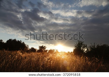 sunset with clouds over field at autumn - stock photo