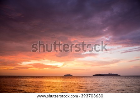 Sunset with dramatic clouds on the tropical beach while magic hour. - stock photo